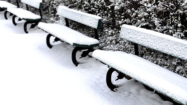 オフシーズンで雪が積もったベンチ